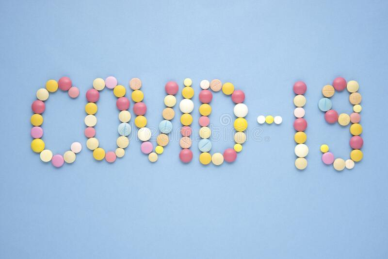COVID - 19. Creative healthcare and medicine concept photo of covid 19 sign made of drugs and pills on blue background stock photos