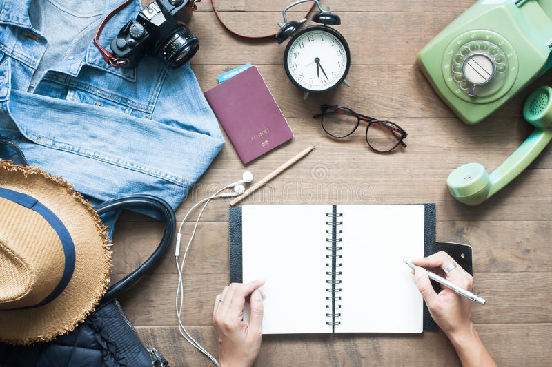Creative high angle view of travel concept with traveler items. And woman hands planning trip on blank notebook royalty free stock photo