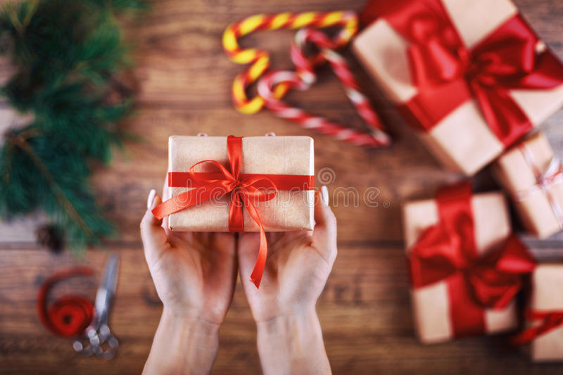 Creative hobby. Woman's hands show christmas holiday handmade present in craft paper with ribbon. Making bow at xmas. Gift box. Scissors on wooden table. Top royalty free stock photo
