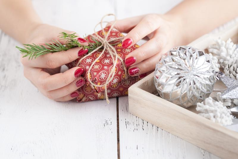 Creative hobby. Woman`s hands wrap christmas holiday handmade present in craft paper with twine ribbon. Making bow at xmas gift b stock photography