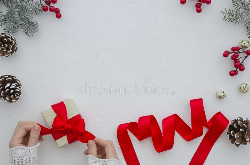 Creative hobby. Woman`s hands wrap christmas holiday handmade present with red ribbon. Making bow gift box, decorated royalty free stock images