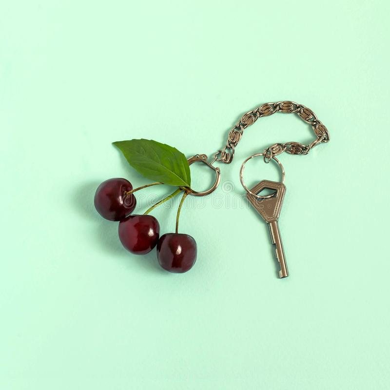 Creative idea: cherry as keychain with key. Cherry as keychain with key on pastel green background. Minimal style. Creative idea, imagination and fantasy stock images