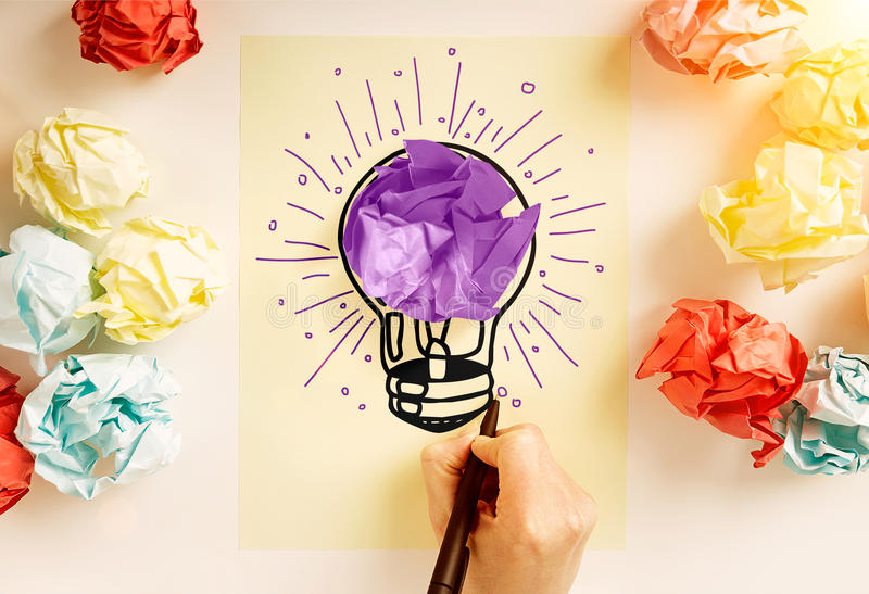 Creative idea. Concept with hand drawing abstract purple lightbulb sketch on paper sheet surrounded with colorful crumpled paper balls stock images