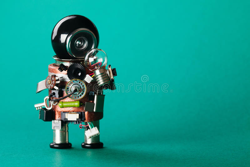 Creative idea concept. Robot looking at light bulb. retro style toy character with funny black helmet head. Copy space, green back stock photos