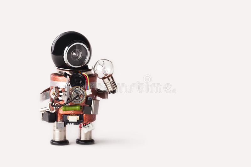 Creative idea inspiration concept. Robot handyman with lamp bulb. Creative design cyborg toy, funny black helmet head stock photo