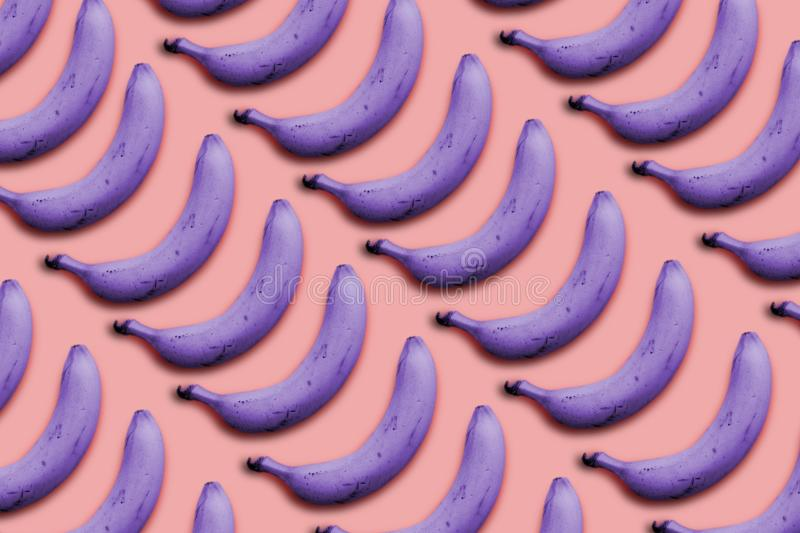 Creative idea in a surrealistic style purple bananas on a pink background stock image