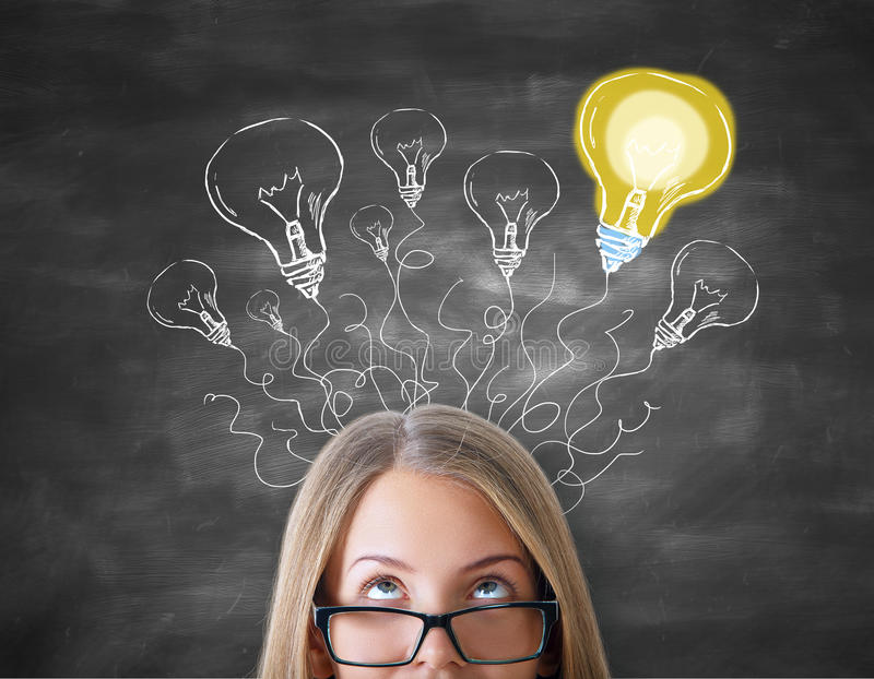 Creative ideas concept. Attractive caucasian girl with abstract light bulb maze on chalkboard background. Creative ideas concept royalty free illustration