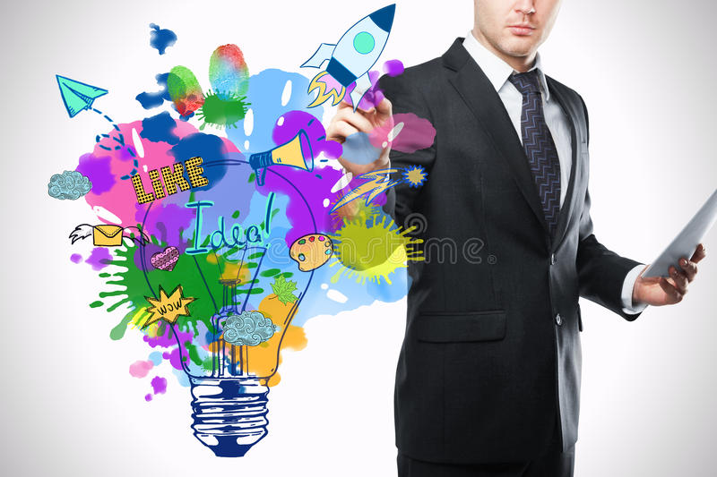 Creative ideas concept. Businessman drawing colorful lamp sketch. Creative ideas concept royalty free stock photography