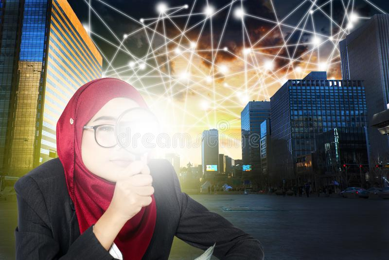 Businesswomen searching using her magnifier over abstract cityscape and connection line background royalty free stock photography