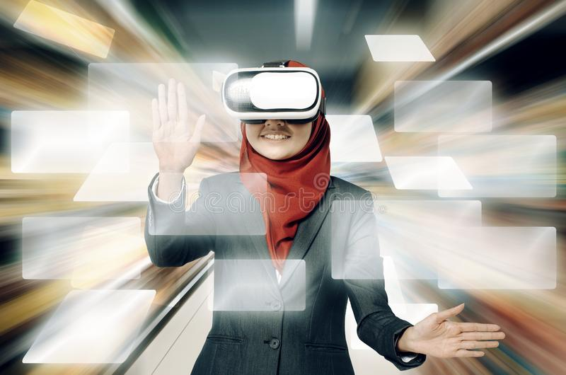 Successful young muslimah businesswomen wearing virtual reality headset over abstract double exposure background stock photos