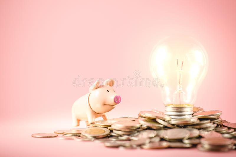 Creative ideas of saving money concept with lightbulb and piggy bank on coins pile. Business planning for the future stock image