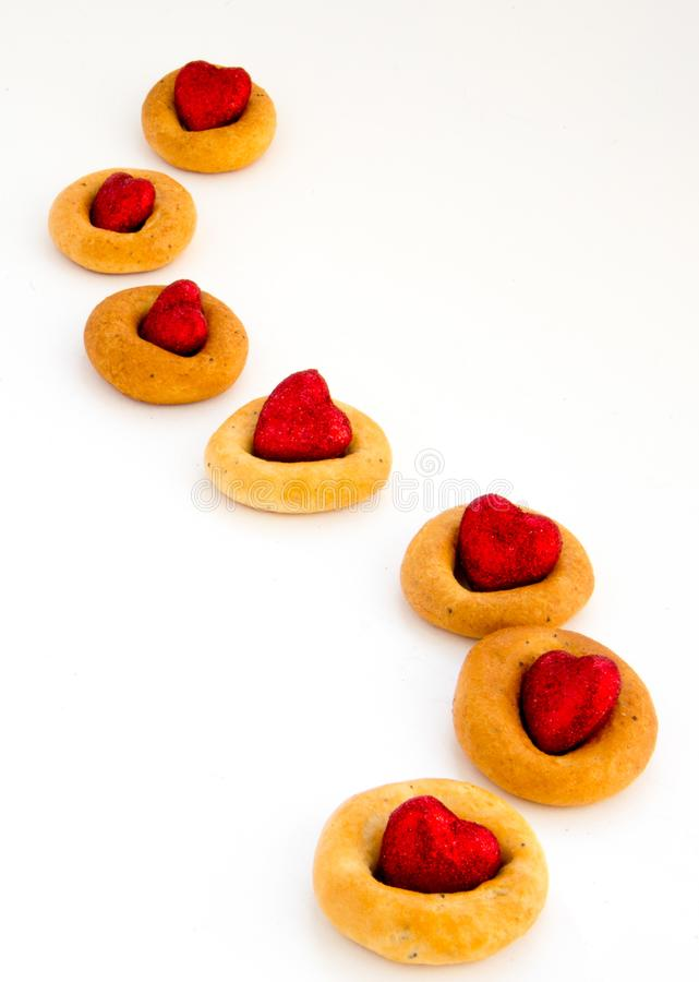 Creative image. Love and friendship. Loneliness, misunderstanding.The concept of Valentine Day. Bread rings on a white background. In combination with red royalty free stock photography