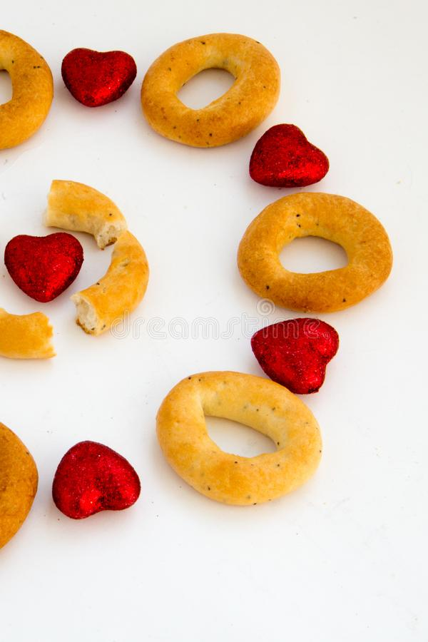 Creative image. Love and friendship. Loneliness, misunderstanding.The concept of Valentine Day. Bread rings on a white background. In combination with red stock photography