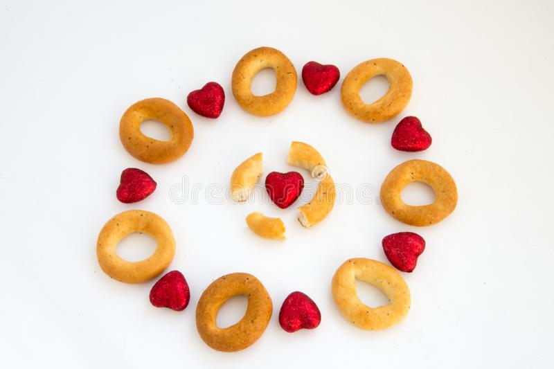 Creative image. Love and friendship. Loneliness, misunderstanding.The concept of Valentine Day. Bread rings on a white background. In combination with red royalty free stock photo