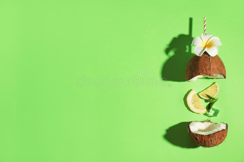 Creative image of summer cocktail made with coconut, lemon slice, mint, ice and straw on green background, top view stock photos