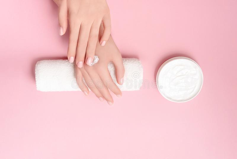 Creative image of woman moisturizing her hands with cosmetic cream with copy space on pink background in minimalistic royalty free stock images