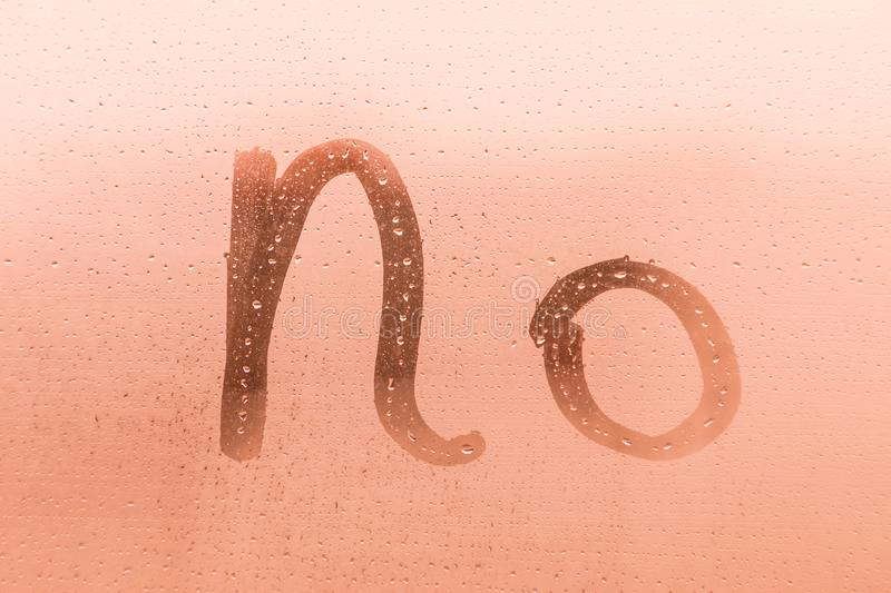The creative inscription no on the orange or pink evening or morning window glass stock photography