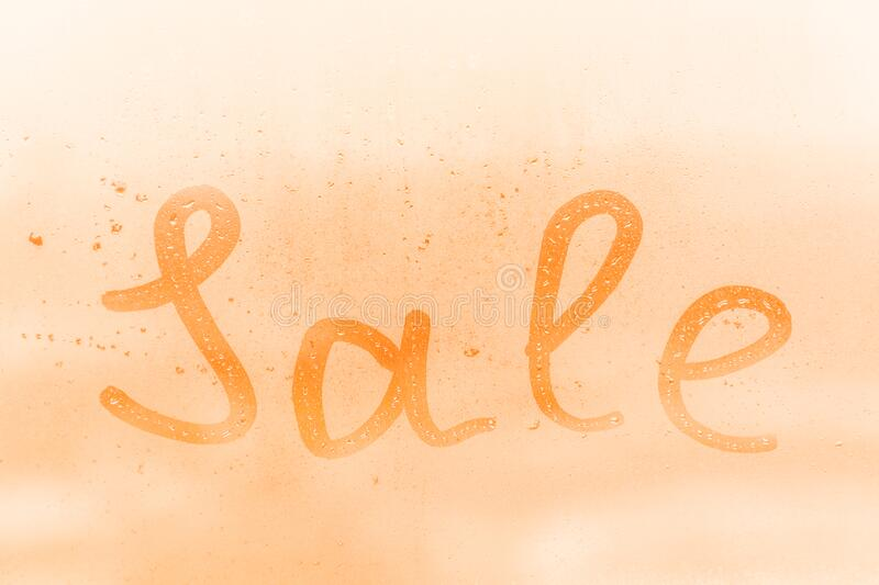 The creative inscription sale on the orange or pink evening or morning window glass. With drops stock photo