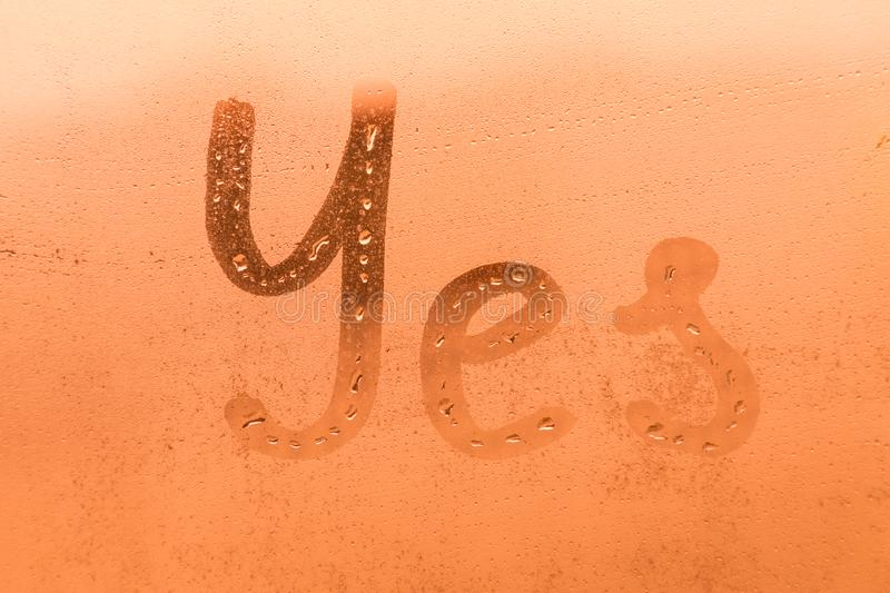 The creative inscription yes on the orange or pink evening or morning window glass royalty free stock photo