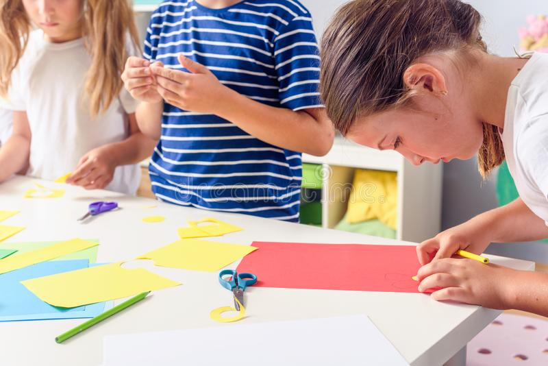 Creative kids. Creative Arts and Crafts Classes in After School Activities. Creative projects with children at home or at school. Kids making some paper crafts royalty free stock photo