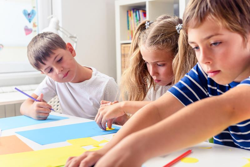 Creative kids. Creative Arts and Crafts Classes in After School Activities. Creative projects with children at home or at school. Kids making some paper crafts stock photos