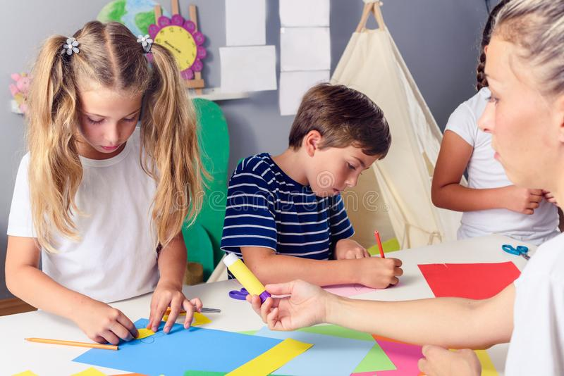 Creative kids. Creative Arts and Crafts Classes in After School Activities. Creative projects with children at home or at school. Kids making some paper crafts royalty free stock images