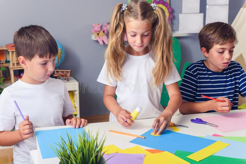 Creative kids. Creative Arts and Crafts Classes in After School Activities. Creative projects with children at home or at school. Kids making some paper crafts royalty free stock photography
