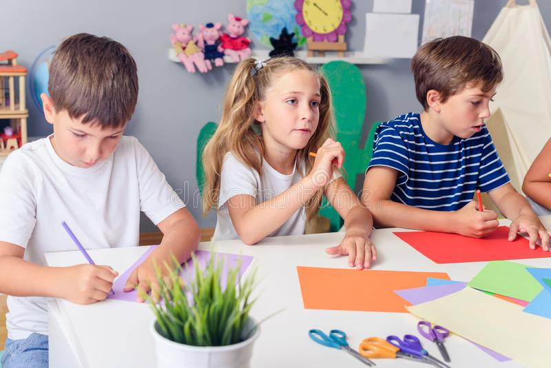 Creative kids. Creative Arts and Crafts Classes in After School Activities. Creative projects with children at home or at school. Kids making some paper crafts stock photo