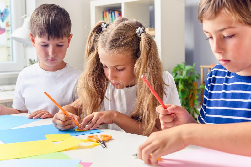 Creative kids. Creative Arts and Crafts Classes in After School Activities. Creative projects with children at home or at school. Kids making some paper crafts royalty free stock photos