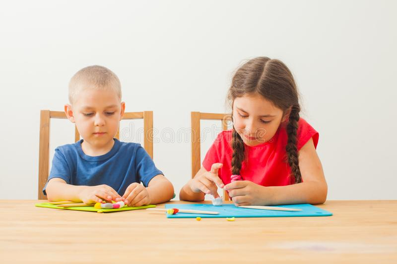 Creative kids molding at the table home stock images