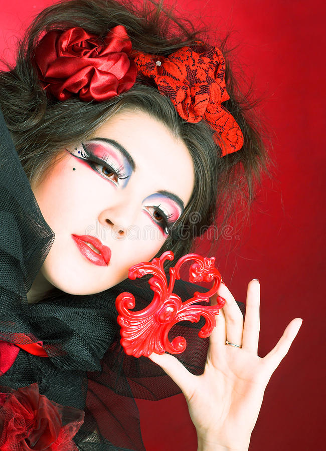Creative lady. Queen of hearts. Creative lady in black and red colors and with bright make-up stock photography