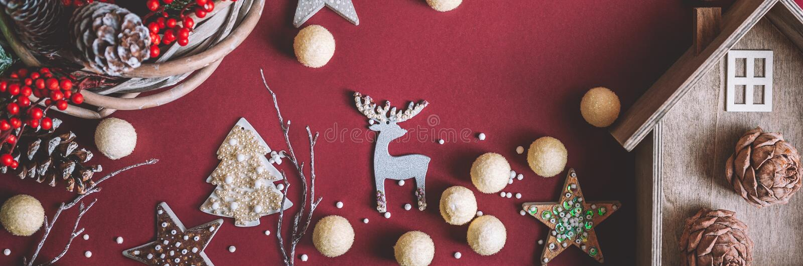 Creative layout banner merry christmas and new year holidays on burgundy paper background decorative house of a deer and wreath royalty free stock photography