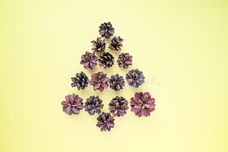 Creative layout of Christmas tree made of fir cones with free space note on yellow. Flat lay. Nature New Year concept royalty free stock photography