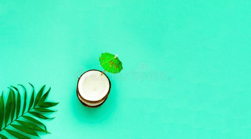 Creative layout of coconuts mit decorative umbrella on green background.Copy space. Creative layout of coconuts mit decorative umbrella on green background. Copy stock image