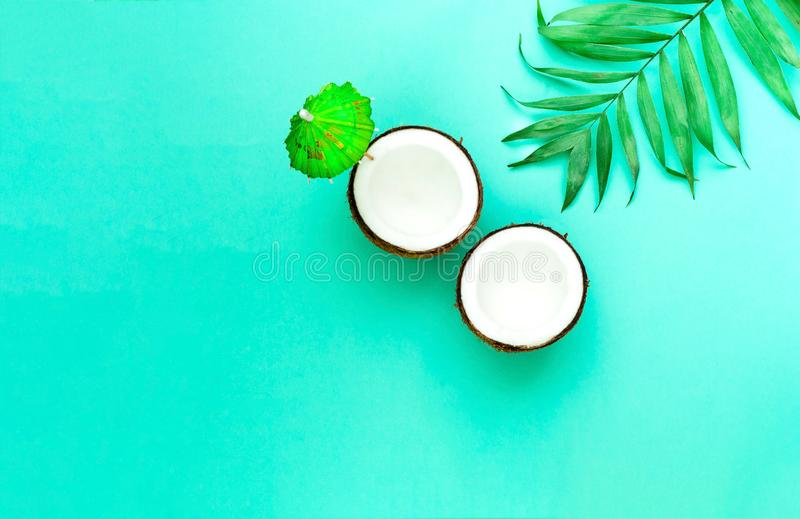 Creative layout of coconuts mit decorative umbrella on green background.Trendy color 2020. Copy space. Close-up stock photos