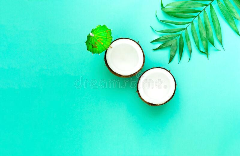 Creative layout of coconuts mit decorative umbrella on green background.Trendy color 2020. Copy space. Close-up royalty free stock photos