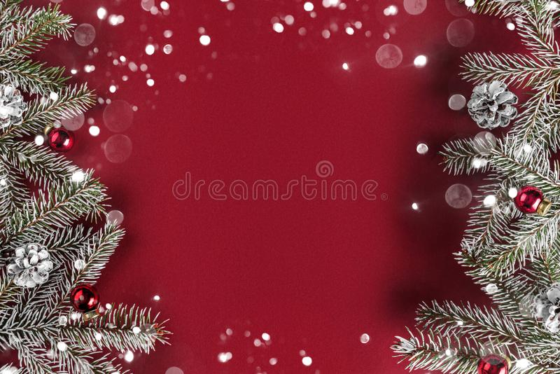 Creative layout frame made of Christmas fir branches, pine cones, gifts, red decoration on red background. Xmas and New Year theme, bokeh, glowing. Flat lay royalty free stock photos