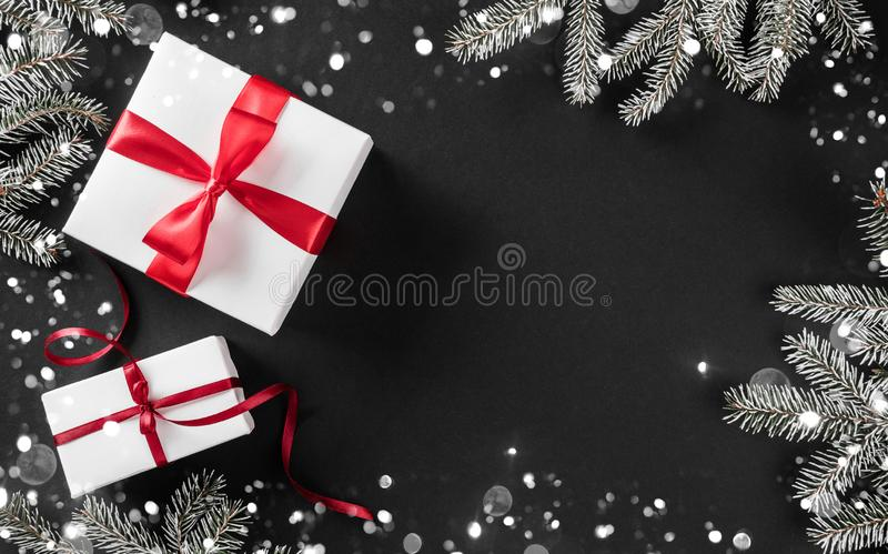 Creative layout frame made of Christmas tree branches, pine cones, gifts with red ribbon on dark background. royalty free stock photography