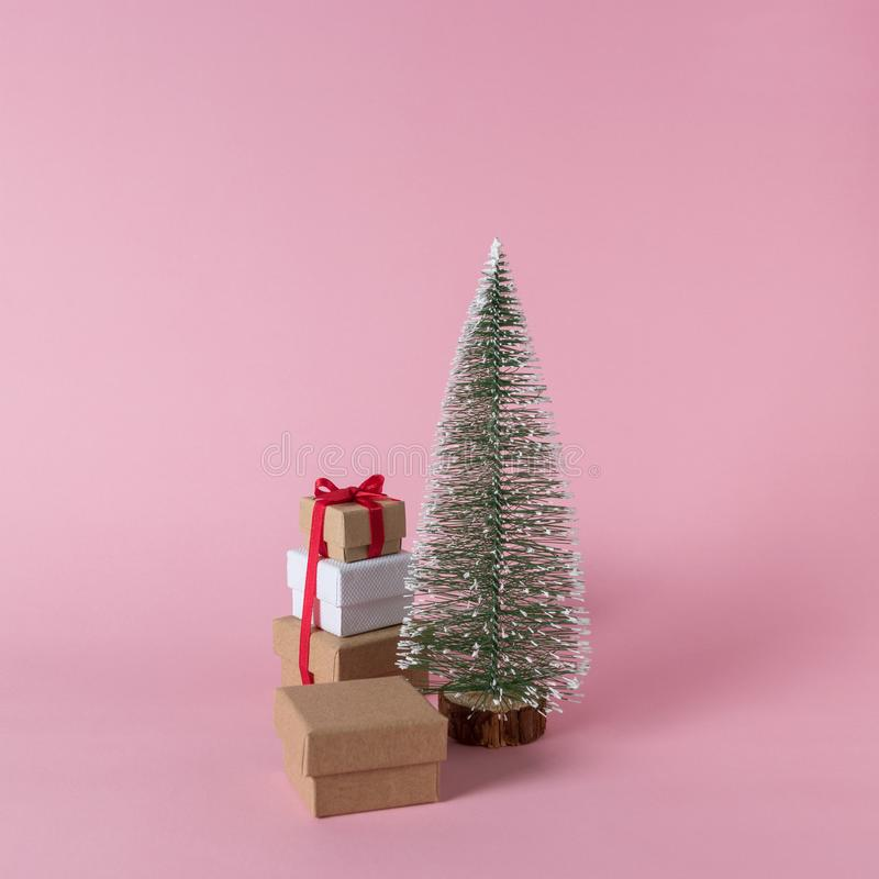 Creative layout of gift boxes and Christmas tree on pink background. royalty free stock photography