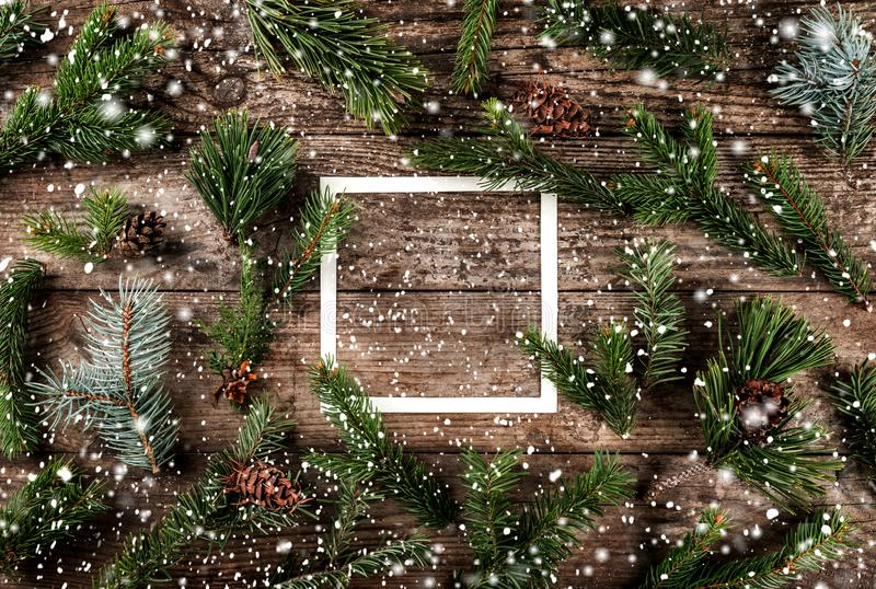 Creative layout made of Christmas fir branches with frame of paper card note, pine cones and snowflakes on wooden background stock photo