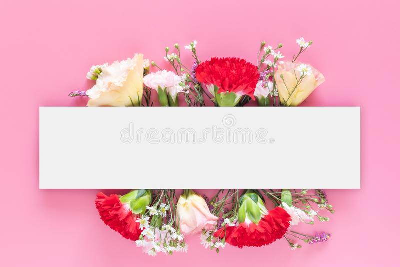 Creative layout made with fresh colorful spring flowers on bright pink background with white rectangle bar banner label. Wedding invitation, posters or royalty free stock photo