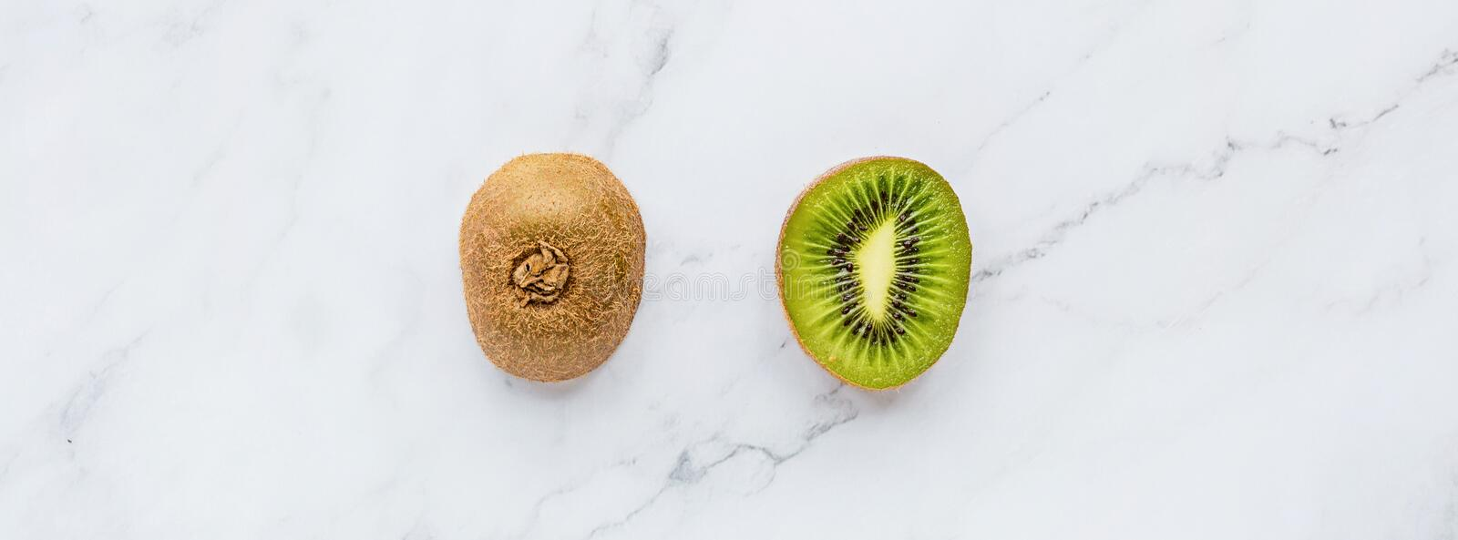 Creative layout made of fresh kiwi on white marble background. Tropical flat lay. Food concept. Mockup, top view, place for text, royalty free stock photo