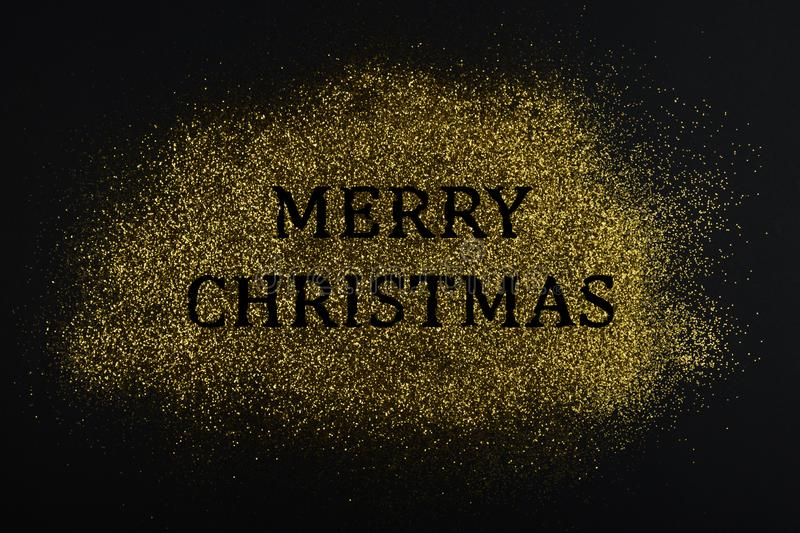 Creative layout made of golden glitter with sign `Merry Christmas` on black paper background. stock image