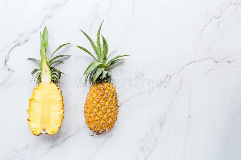 Creative layout made of pineapple on white marble background. Tropical flat lay. Food concept. Mockup, top view, place for text, stock photography