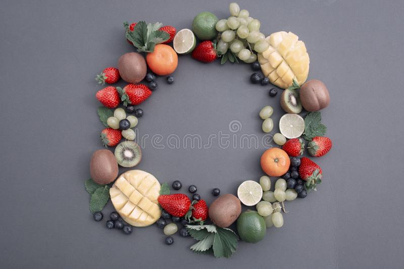 Creative layout made of summer fruits, frame. Tropical flat lay. Grapes, mango, strawberry, blueberry, kiwi, mint, lime, citrus royalty free stock photos