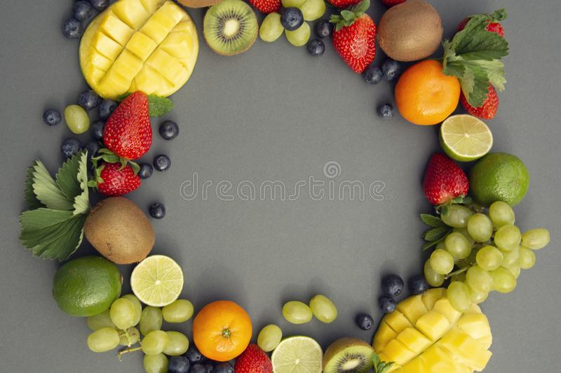 Creative layout made of summer fruits, frame. Tropical flat lay. Grapes, mango, strawberry, blueberry, kiwi, mint, lime, citrus stock images