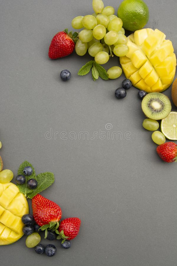 Creative layout made of summer fruits, frame. Tropical flat lay. Grapes, mango, strawberry, blueberry, kiwi, mint, lime, citrus. Creative layout made of summer royalty free stock photos