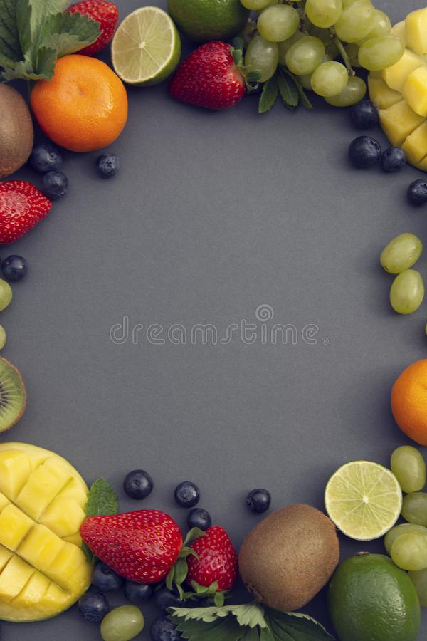 Creative layout made of summer fruits, frame. Tropical flat lay. Grapes, mango, strawberry, blueberry, kiwi, mint, lime, citrus stock photography