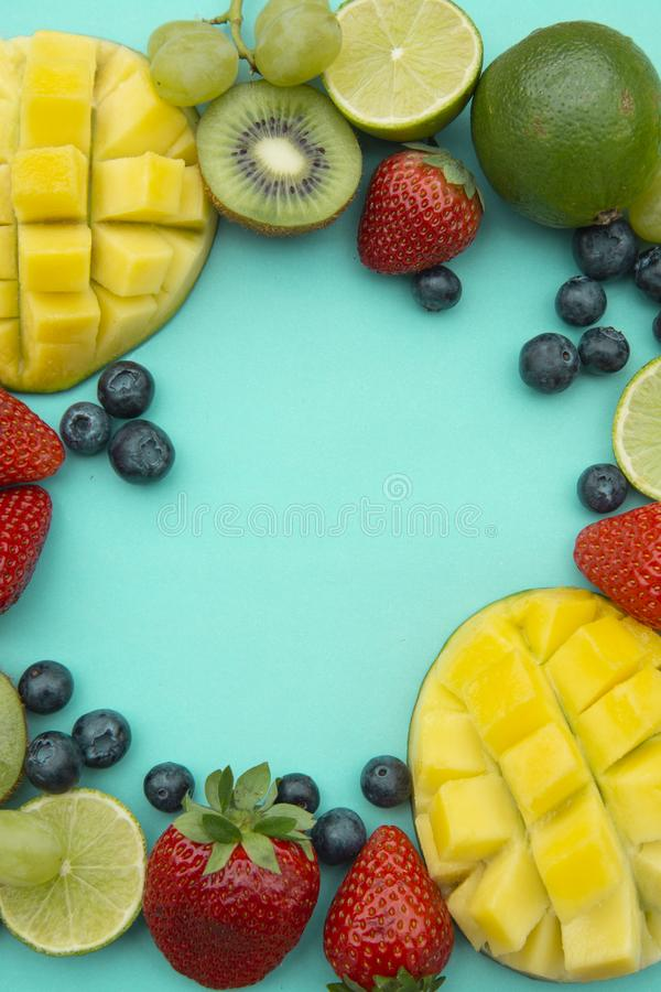 Creative layout made of summer fruits, frame. Tropical flat lay. Grapes, mango, strawberry, blueberry, kiwi, mint, lime, citrus. Creative layout made of summer royalty free stock image