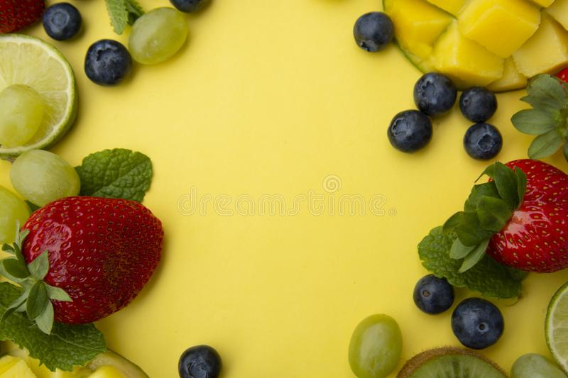 Creative layout made of summer fruits, frame. Tropical flat lay. Grapes, mango, strawberry, blueberry, kiwi, mint, lime, citrus royalty free stock photo